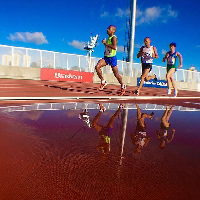 Três atletas em movimento de corrida, com sua imagens refletidas em um espelho d'Água com da pista vermelha e o céu azul.