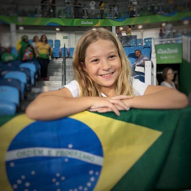 menina torcedora com os braços dobrados em cima da bandeira do Brasil