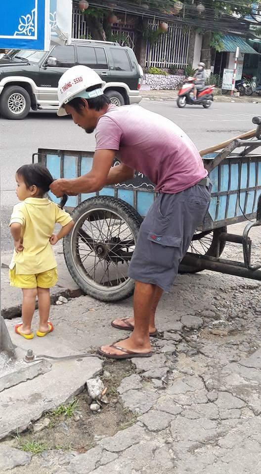 Hình ảnh đáng yêu nhất ngày: Người bố công nhân đứng tỉ mẩn cột tóc cho cô con gái nhỏ - Ảnh 1.