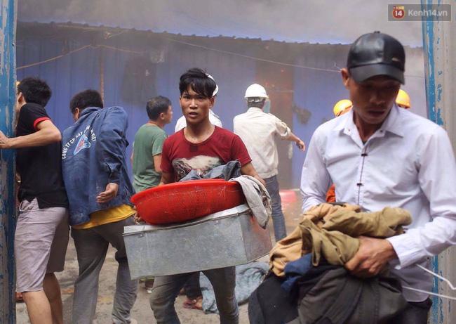 Các công nhân ôm đồ đạc chạy khỏi đám cháy