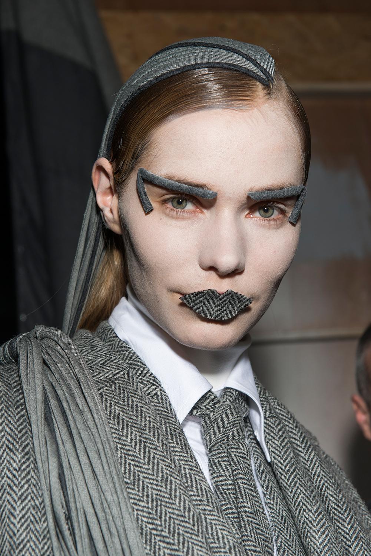 Như thể việc đánh phấn trắng bệch còn chưa đủ đáng sợ, các người mẫu trong show diễn Thom Browne còn phải gắn vải lên lông mày và môi như thế này. Và thương hiệu Mỹ đã thành công trong việc dọa ma khán giả.