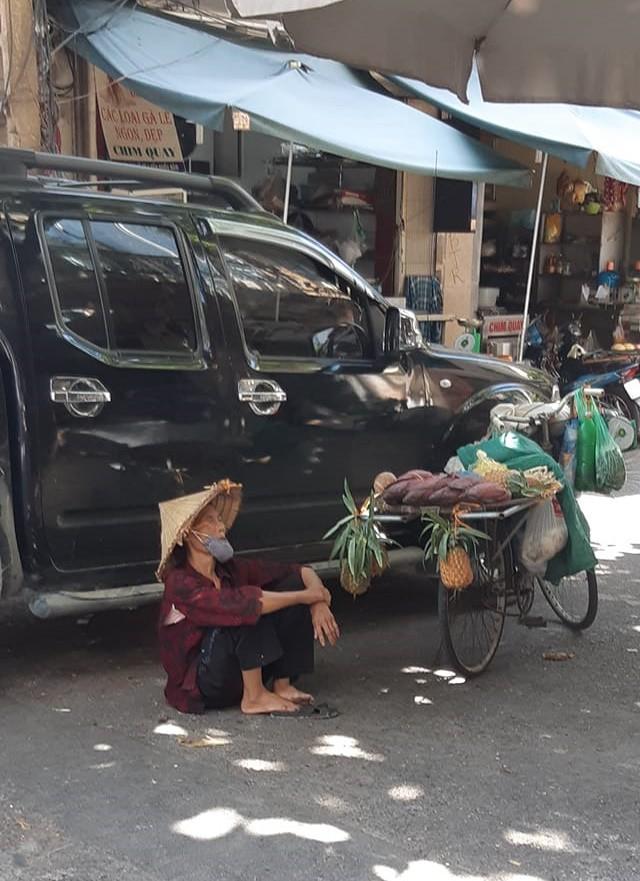 Hình ảnh bà cụ bán hàng rong ngồi nghỉ dưới bóng râm giữa cái nắng cháy da cháy thịt của Thủ đô khiến nhiều người thương cảm - Ảnh 2.