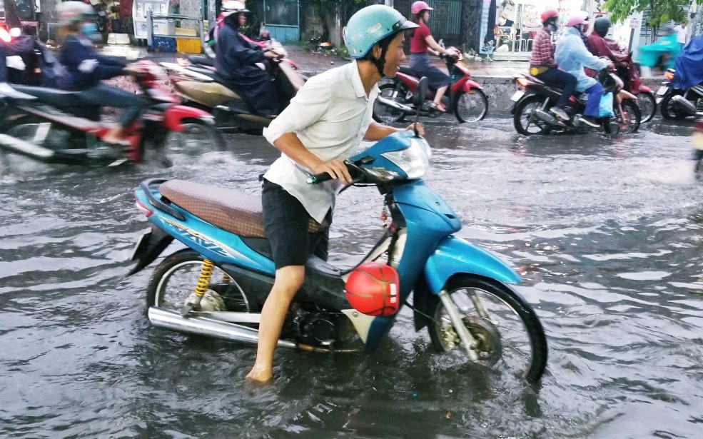 Người dân bì bõm lội nước đẩy xe về nhà vì nhiều tuyến đường ở Sài Gòn bị ngập nặng