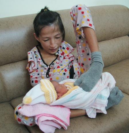 Cảm phục người mẹ trẻ chăm con bằng... hai chân 1