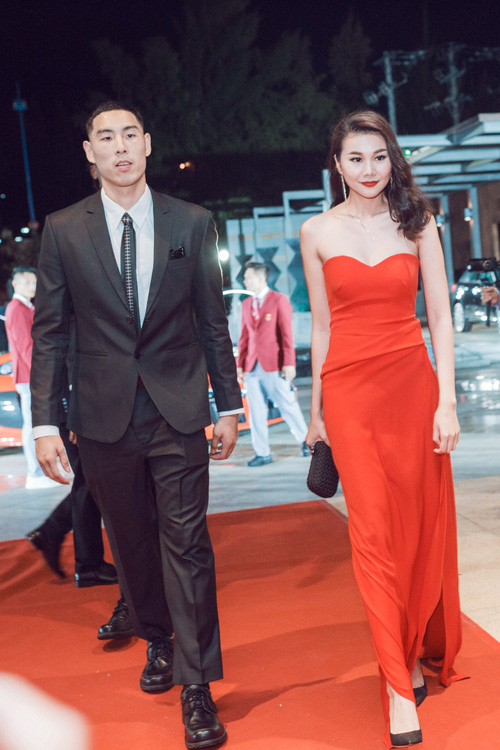 Thanh Hằng khoe vai trần trong chiếc đầm đỏ nổi bật. Chân dài được một cầu thủ ngoại hộ tống đến sự kiện.