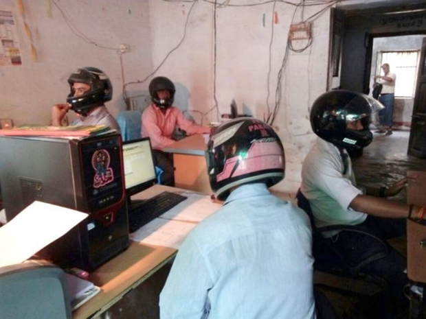 Sợ trần nhà sập vào đầu, nhân viên văn phòng Ấn Độ đồng loạt đội mũ bảo hiểm để bảo toàn tính mạng - Ảnh 1.