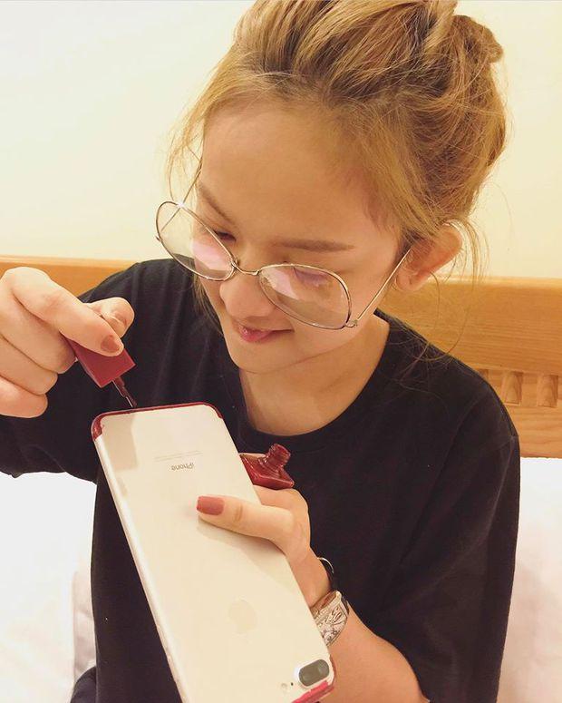 Muốn có iPhone đỏ, Thuý Vi dùng sơn móng tay và giấy dán màu để... làm mới điện thoại - Ảnh 1.