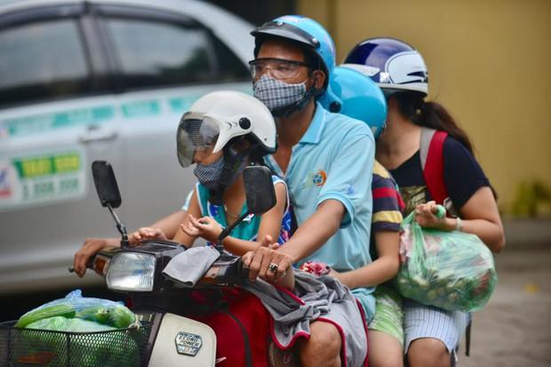 Một gia đình di chuyển bằng xe máy mang theo khá nhiều quà quê. Ảnh: Phương Thảo