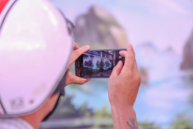 Một người đàn ông dừng bên đường để chụp bức tranh Vịnh Hạ Long.