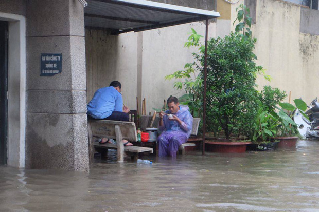 Chùm ảnh: Người Hà Nội mặc áo mưa ăn trưa giữa đường phố ngập lênh láng - Ảnh 2.