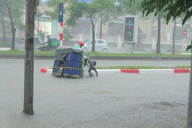 Chùm ảnh: Người Hà Nội mặc áo mưa ăn trưa giữa đường phố ngập lênh láng - Ảnh 7.