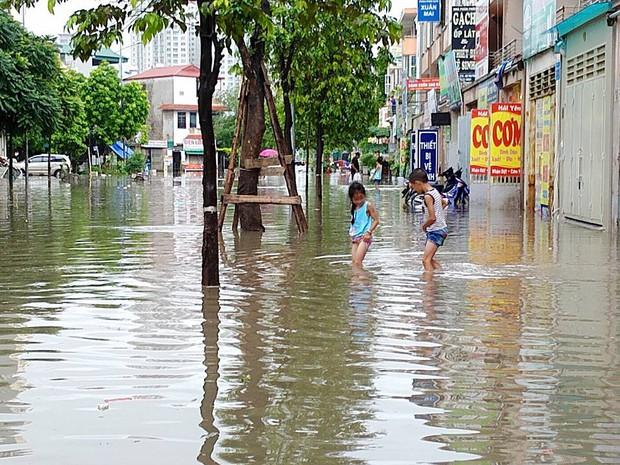 Chùm ảnh: Người Hà Nội mặc áo mưa ăn trưa giữa đường phố ngập lênh láng - Ảnh 11.