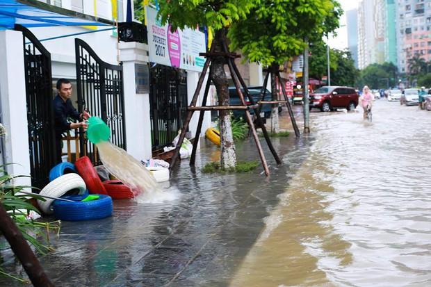 Chùm ảnh: Người Hà Nội mặc áo mưa ăn trưa giữa đường phố ngập lênh láng - Ảnh 12.