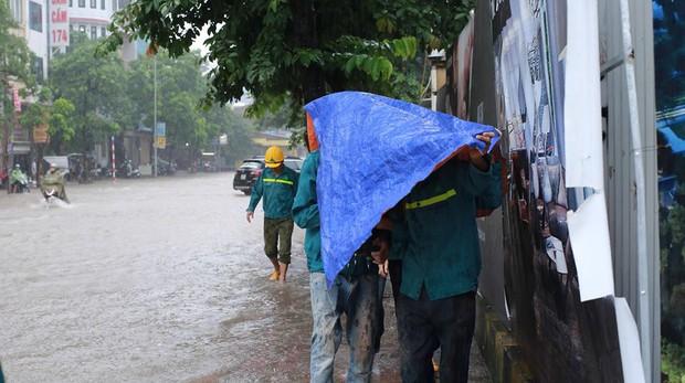 Chùm ảnh: Người Hà Nội mặc áo mưa ăn trưa giữa đường phố ngập lênh láng - Ảnh 5.