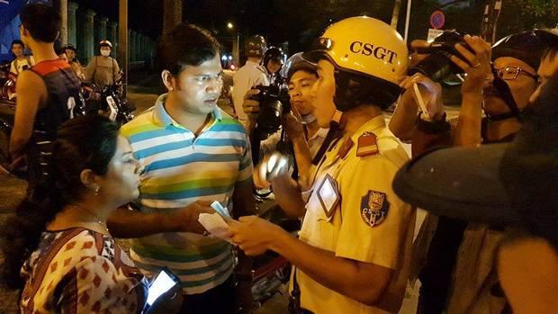 Chiến sĩ CSGT giúp ông Đoàn Ngọc Hải phiên dịch, trao đổi cùng 2 du khách người Ấn Độ.