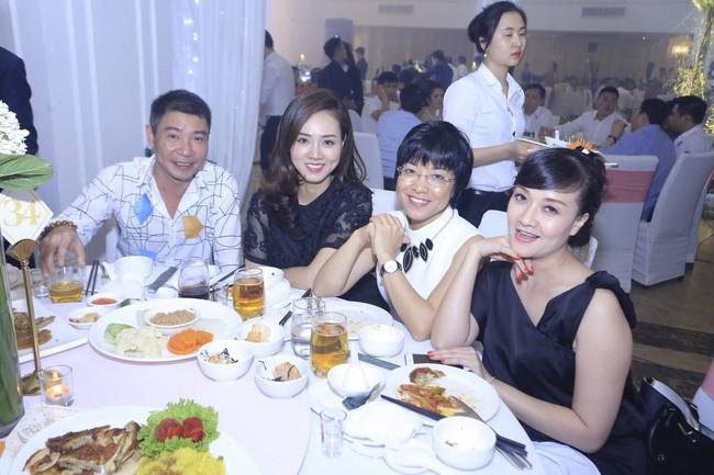 3 người vui vẻ ngồi cạnh nhau trên bàn tiệc