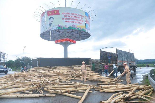 Xe chở 10 tấn gỗ lật nghiêng, chiến sỹ CSGT hỗ trợ tài xế bốc dỡ gỗ khỏi lòng đường - Ảnh 2.