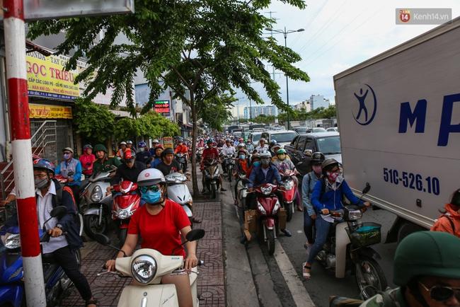 Kẹt xe kéo dài hơn 2km trên đại lộ Phạm Văn Đồng sau cơn mưa lớn ở Sài Gòn - Ảnh 5.