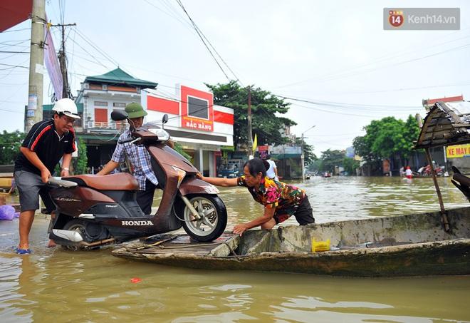 Chùm ảnh: Kiếm bộn tiền từ việc chèo đò qua điểm ngập nặng trong đợt lụt lịch sử tại Ninh Bình - ảnh 11