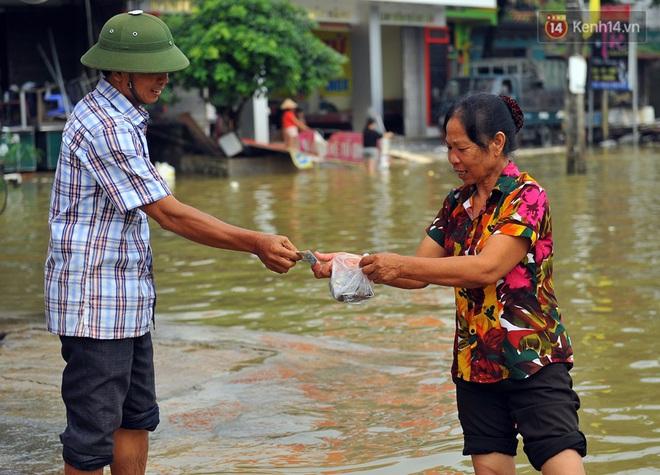 Chùm ảnh: Kiếm bộn tiền từ việc chèo đò qua điểm ngập nặng trong đợt lụt lịch sử tại Ninh Bình - ảnh 12