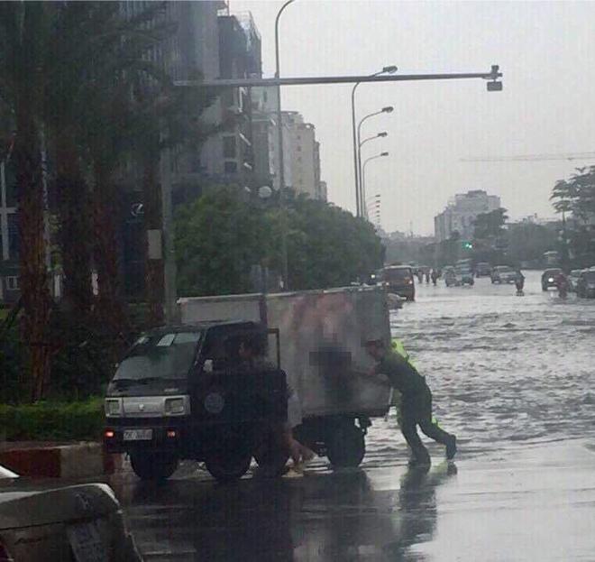 Hành động đẹp: Công an Hà Nội giúp tài xế đẩy chiếc xe tải bị chết máy trong trời mưa bão - Ảnh 2.