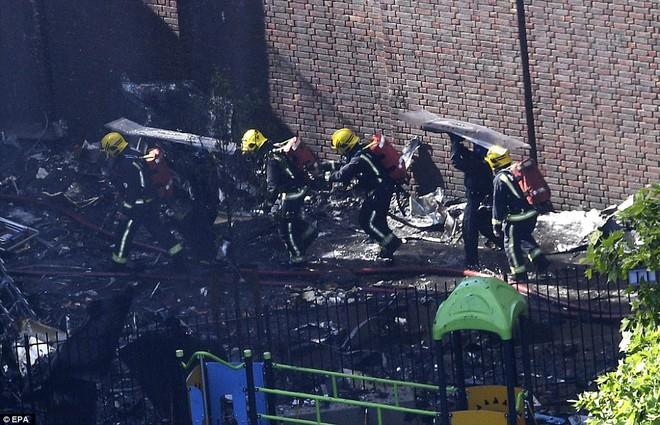 Không một ai ở 3 tầng trên cùng sống sót: Những thi thể đầu tiên được đưa ra khỏi tòa tháp 27 tầng sau vụ cháy - Ảnh 3.