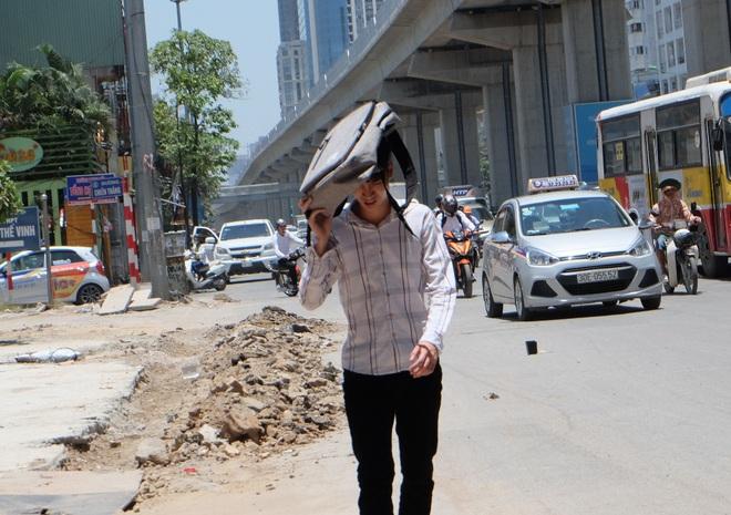 Người Hà Nội quấn chăn, quần áo kín mít tránh nắng nóng kỷ lục trong 40 năm qua - Ảnh 3.