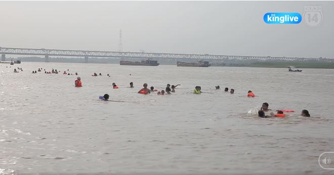 Clip: Hàng trăm người dân và trẻ nhỏ đổ ra bãi cát ven sông Hồng tắm giải nhiệt bất chấp biển cấm - ảnh 4