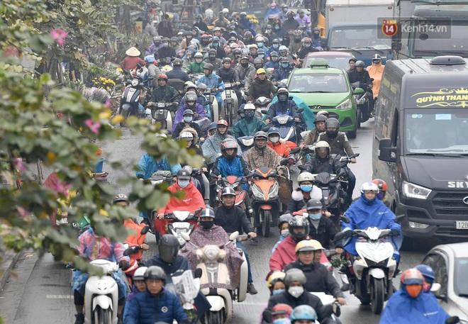 Chùm ảnh: Trẻ nhỏ trùm chăn, khoác áo mưa chật vật theo chân bố mẹ rời Thủ đô về quê ăn Tết - ảnh 9