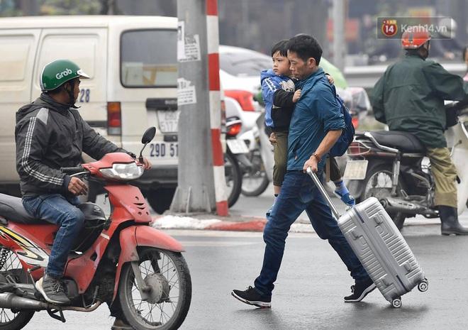 Chùm ảnh: Trẻ nhỏ trùm chăn, khoác áo mưa chật vật theo chân bố mẹ rời Thủ đô về quê ăn Tết - ảnh 13