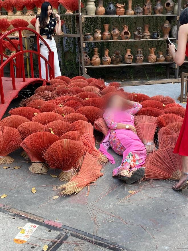 Khoảng sân xếp đầy những bó hương bị 2 người phụ nữ nằm đè lên để chụp ảnh, dân mạng chán ngán: Mặc áo dài mà không có chút duyên nào - Ảnh 1.