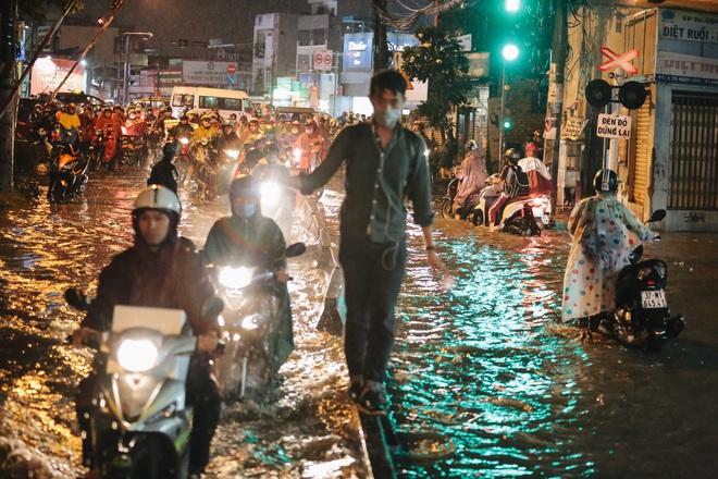 Người Sài Gòn vật lộn với đường ngập lút bánh xe, nước chảy cuồn cuộn như thác trong đêm mưa lớn - Ảnh 18.