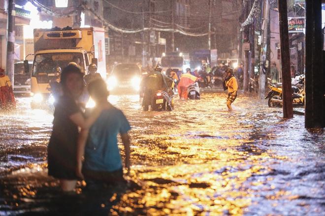 Người Sài Gòn vật lộn với đường ngập lút bánh xe, nước chảy cuồn cuộn như thác trong đêm mưa lớn - Ảnh 3.