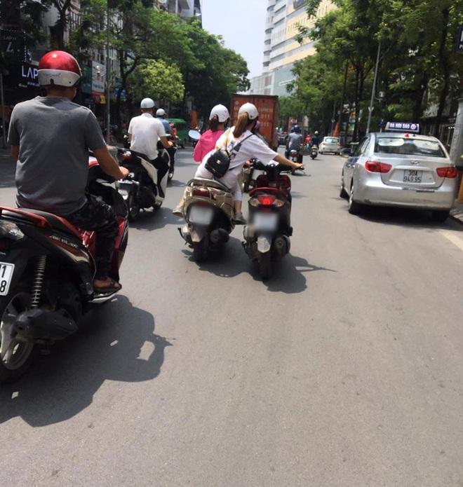 Pha dắt xe cồng kềnh của 2 cô gái trên đường phố Hà Nội khiến nhiều người thót tim: Ai lại mang lý thuyết dắt xe đạp để dắt xe máy thế này - Ảnh 1.