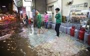 Người Sài Gòn dùng bình gas, thùng bia chắn trước cửa để ngăn nước tràn vào nhà sau cơn mưa lớn