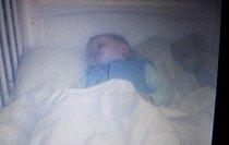 Đặt camera để quan sát con ngủ, bố mẹ giật mình nhìn thấy bóng trắng kỳ lạ nằm kế bên