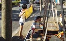 """Bé gái """"đội cả bầu trời"""" cầm khăn đứng che chắn cho bố sửa xe giữa trời nắng"""