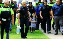 Câu chuyện buồn đằng sau bức hình em bé 4 tuổi đi khai giảng với 18 cảnh sát theo sau