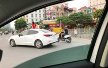 Clip: Hai bé gái thản nhiên ngồi vắt vẻo trên nóc ô tô đang đi trên đường