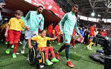 Ronaldo như một người cha, ân cần đẩy xe lăn cho cô bé mascot khuyết tật