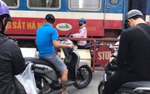 Bức ảnh gây căng thẳng: Cô gái đi xe máy đứng trong khe hẹp giữa đoàn tàu đang chạy và rào chắn