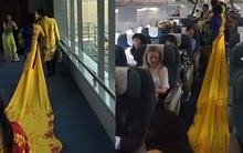 Vợ MC Thanh Bạch diện áo dài như đuôi công lên máy bay khiến nhiều hành khách choáng