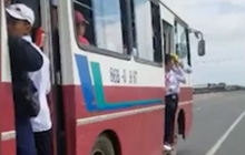 Học sinh bám trên cửa ô tô đang chạy tốc độ cao trên quốc lộ ở Bình Thuận