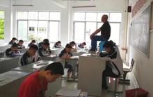 Quá mệt mỏi với những mánh khoé thi cử, thầy giáo bê hẳn ghế lên bàn ngồi coi thi như một vị thần khiến học trò sợ xanh mặt