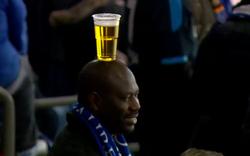 Người đàn ông đặt cốc bia thăng bằng trên đầu, di chuyển quanh khán đài gợi nhớ bà cô đội thúng bánh mỳ ở Việt Nam