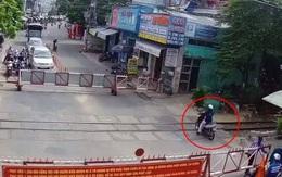 Clip thót tim: Người phụ nữ liều lĩnh đẩy barie, lách xe máy băng qua đường ray khi tàu hỏa đang lao tới