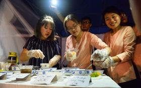 Nhiều gian hàng bán đồ ăn dưới ánh sáng điện thoại tại liên hoan ẩm thực Hà Nội