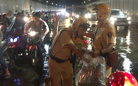 Hình ảnh đẹp đêm trung thu ở Sài Gòn: 2 chiến sĩ CSGT phát áo mưa miễn phí cho người dân trong hầm Thủ Thiêm