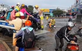Hình ảnh đẹp: CSGT điều xe công vụ chở xe chết máy giúp người dân thoát khỏi đường ngập ở Sài Gòn