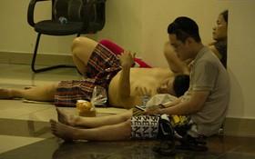 Người dân mệt nhoài nằm khắp vỉa hè, ăn cơm hộp chờ được vào nhà sau những giờ phút hoảng loạn trong vụ cháy chung cư ở Sài Gòn